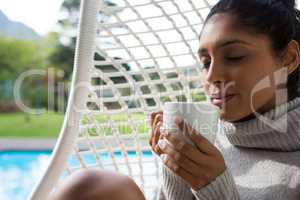 Woman holding coffee cup in swing chair