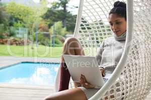 Woman using laptop while resting on swing