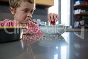 Boy having food in kitchen
