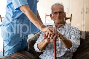 Female doctor standing by senior man sititng on sofa in nursing home