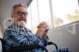 Portrait of senior man sitting on wheelchair in retirement home
