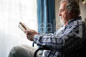 senior man reading book while sitting on wheelchair in nursing home
