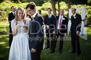 Bride and groom reviewing photographs on mobile phone