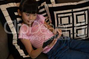 Girl holding remote control on sofa