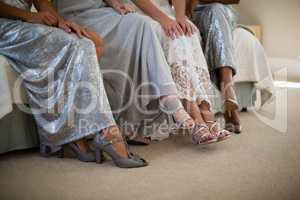 Bride and bridesmaids sitting together on sofa