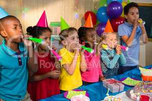 Playful children blowing party horns