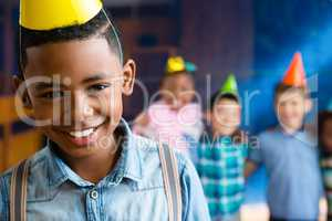 Portrait of boy wearing suspenders with friends in background