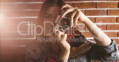 Woman photographing from vintage camera against brick wall