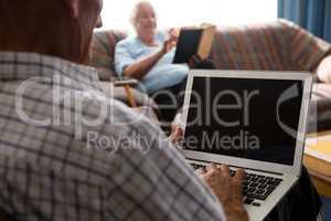 Senior man uisng laptop in nursing home