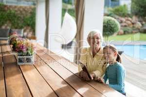 Granddaughter and grandmother sitting in a deck shade with a digital tablet