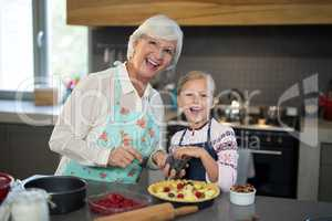 Grandmother and granddaughter posing while adding blue berries to the crust