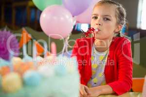 Cute girl blowing party horn during birthday party