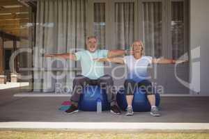 Senior couple doing stretching exercise on exercise ball