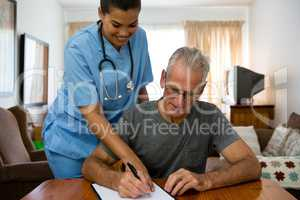 Doctor assisting senior man in writing at nursing home
