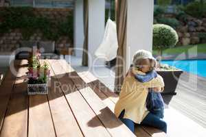 Granddaughter and grandmother embracing in a deck shade