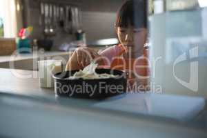 Girl spreading cream on cake seen through glass in kitchen