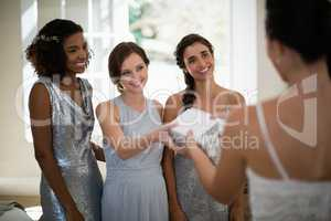 Bride receiving gift from bridesmaid