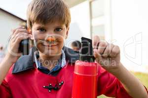 Portrait of boy with face paint using walkie talkie while holding fire extinguisher