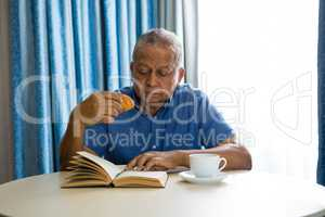 Senior man eating croissant while reading book in nursing home
