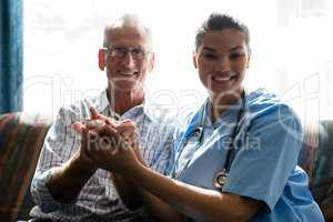Portrait of senior man and female doctor holding hands in nursing home