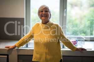 Smiling senior woman standing near kitchen worktop