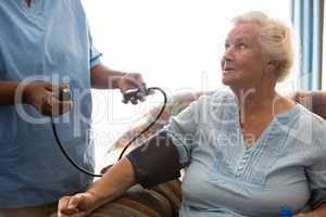 Nurse examining patient in nursing home