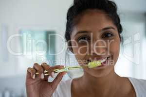 Portrait of woman brushing teeth