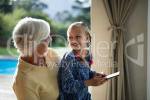Granddaughter and grandmother using a digital tablet in the deck shade