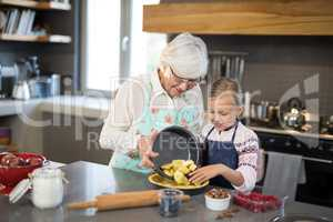 Grandmother and granddaughter adding fresh cut apples to the crust