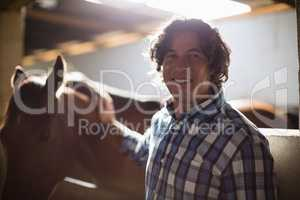 Man caressing the brown horse in the stable