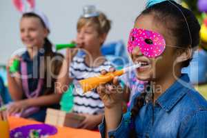 Close up of girl wearing eye mask blowing party horn