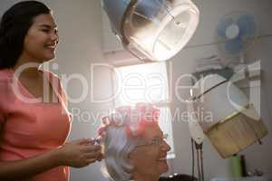 Smiling hairstylist removing curlers from senior woman hair