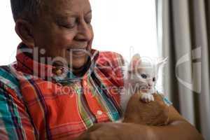 Senior man playing with kitten at nursing home
