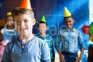 Portrait of boy wearing party hand with friends in background