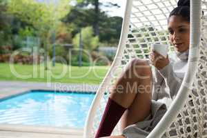 Woman with coffee cup resting in swing chair