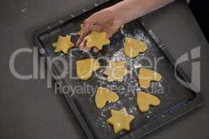 Cropped hand keeping star shape cookie in tray