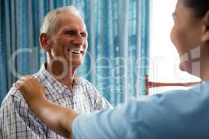 Senior man talking to female doctor in retirement home