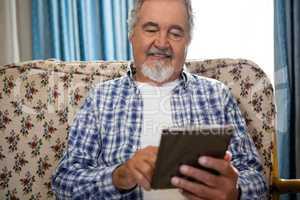 Smiling senior man using digital tablet in nursing home