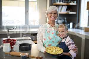 Grandmother and granddaughter posing with fresh cut apples on crust