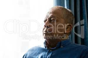 Close up of senior man looking away while sitting by window