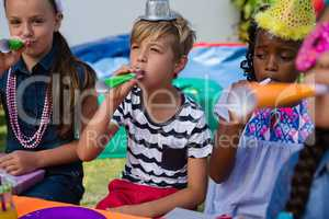 Children blowing part horns