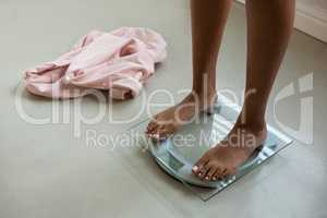 Low section of woman on bathroom scale at home
