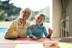 Granddaughter and grandmother drawing in the deck shade near the pool