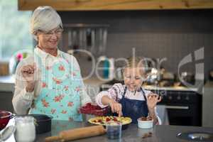 Grandmother and granddaughter adding strawberries to the crust
