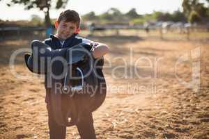 Boy holding horse saddle