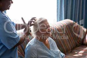 Doctor combing hair of patient in nursing home