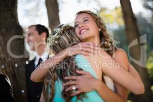 Bride embracing her friend in park