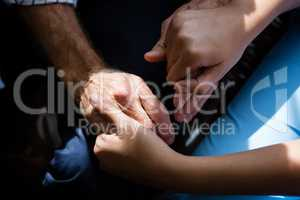 Hands of female doctor consoling senior man in retirement home