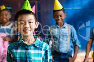 Portrait of smiling boy wearing party hand with friends in background