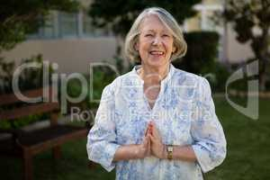 Portrait of happy senior woman standing in prayer position